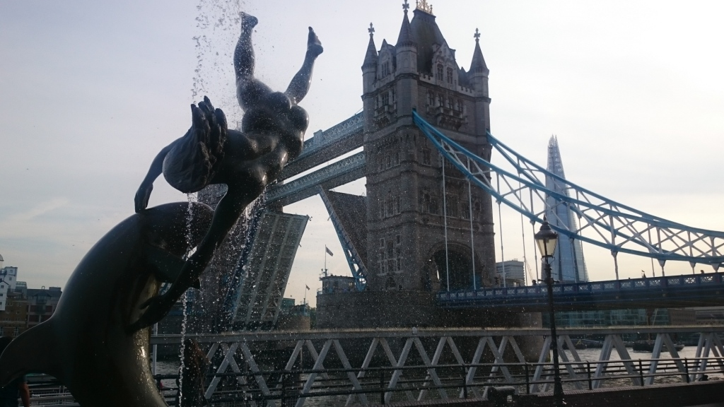 A fountain statue of a girl in london with tower bridge in the back