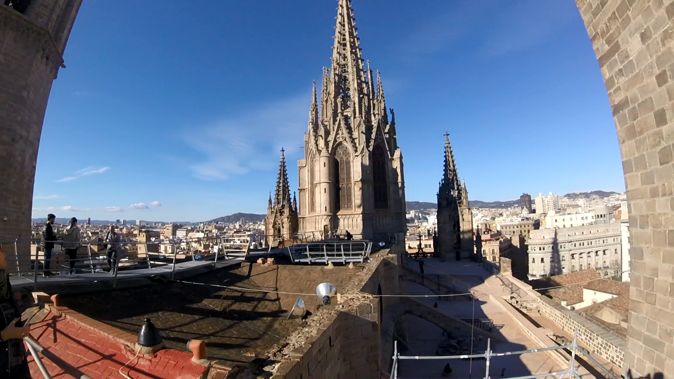 view from the top of the cathedral in barcelona showing 3 towers and a landscape of the city in the background