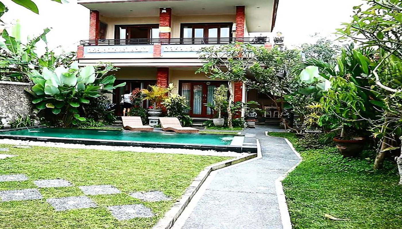 A view of the pool and some of the rooms of Umah Dangin Guest House in ubud, where to stay in Bali, Indonesia, best hotels in ubud, grass, pool, sun chairs and balconies