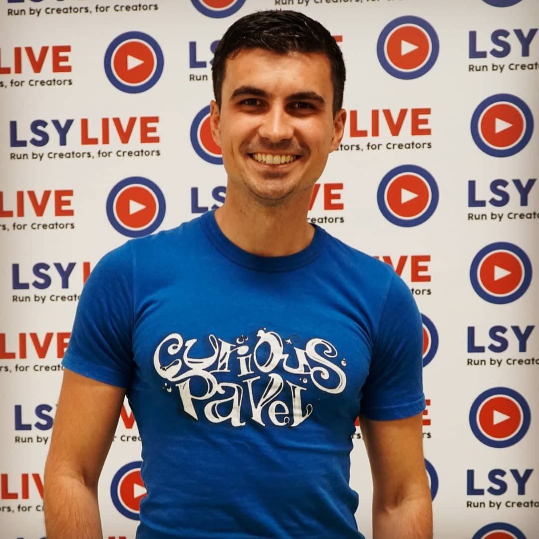 a boy with a blue tshirt saying curious pavel graffiti style in front of a lsylive board