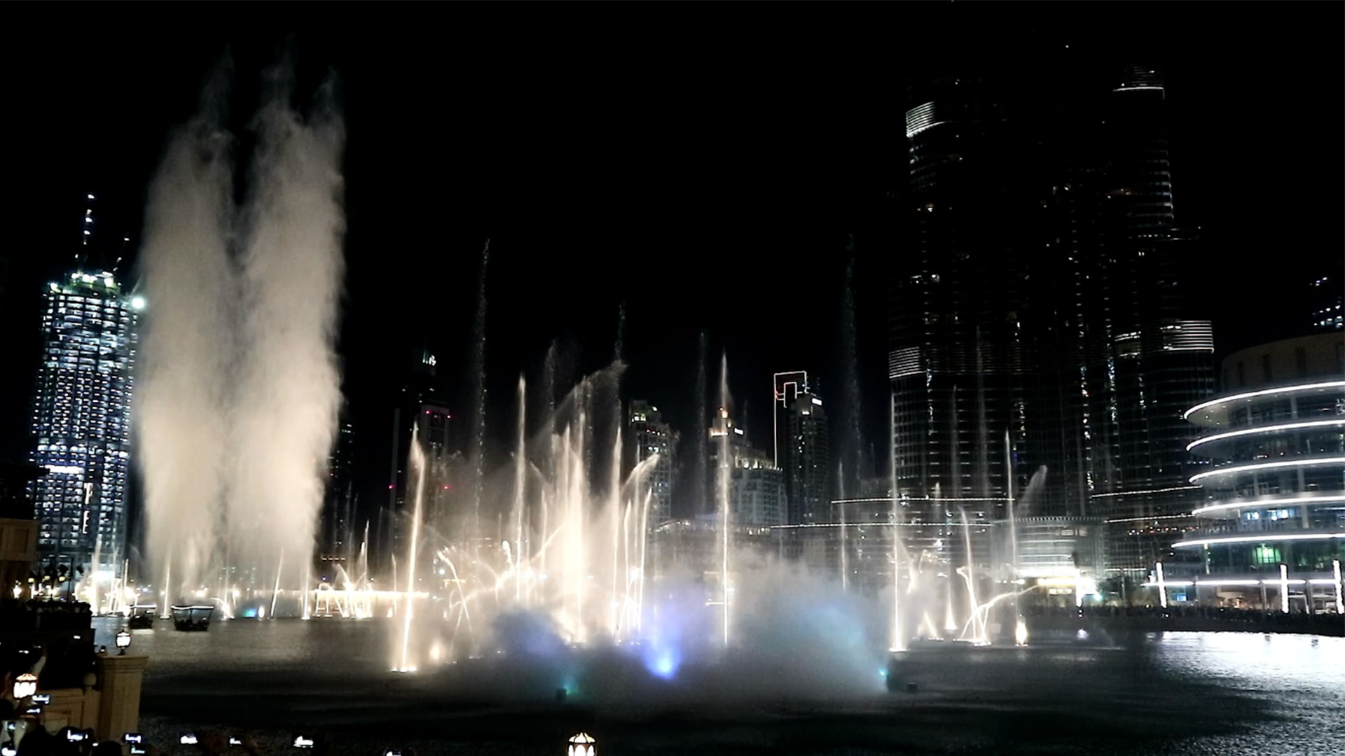 water fountain show in action in dubai downtown happening between burj khalifa and dubai mall