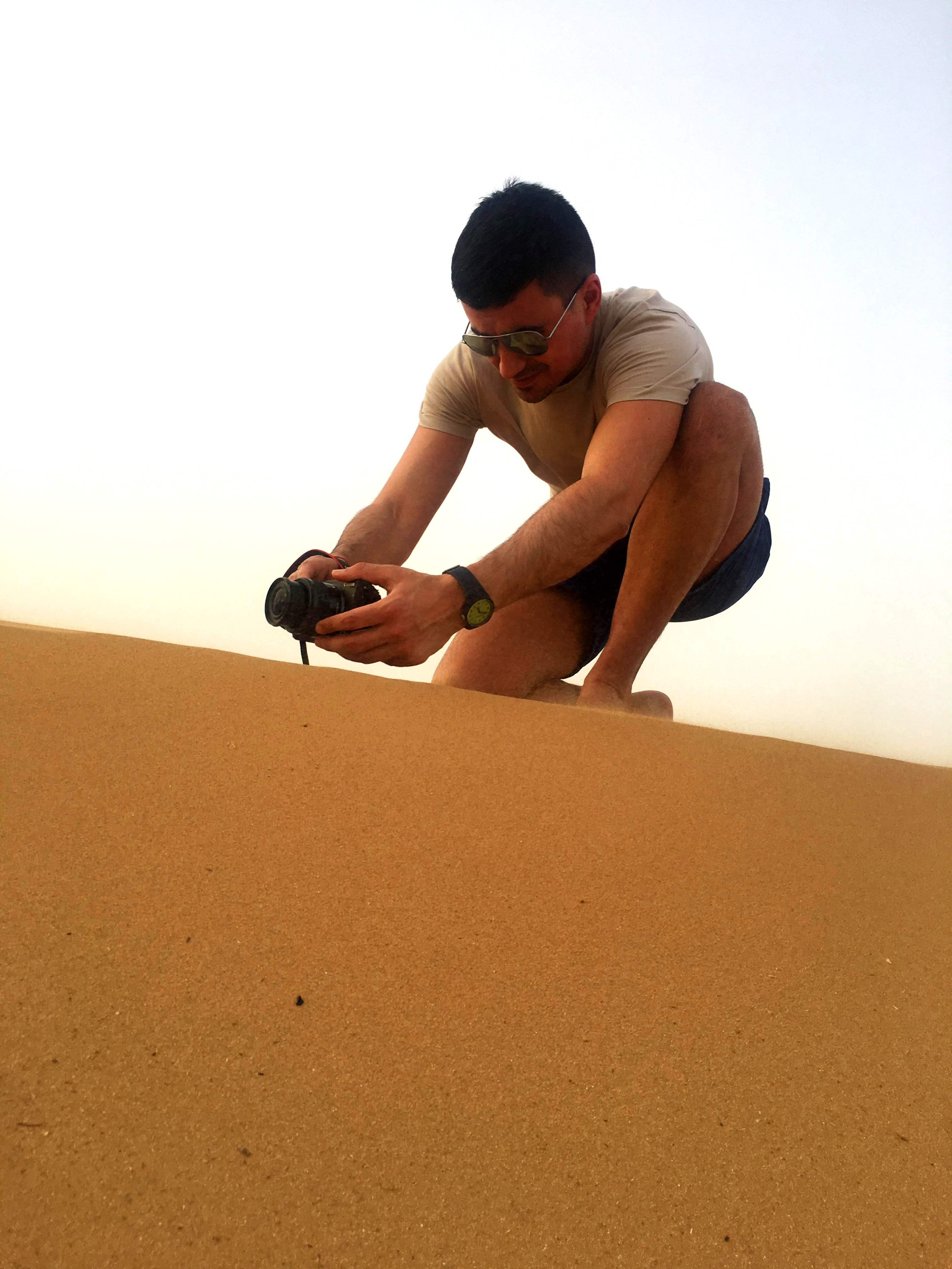 a boy with light colored t-shirt kneeling on a sand dune with a camera in his hands taking a picture
