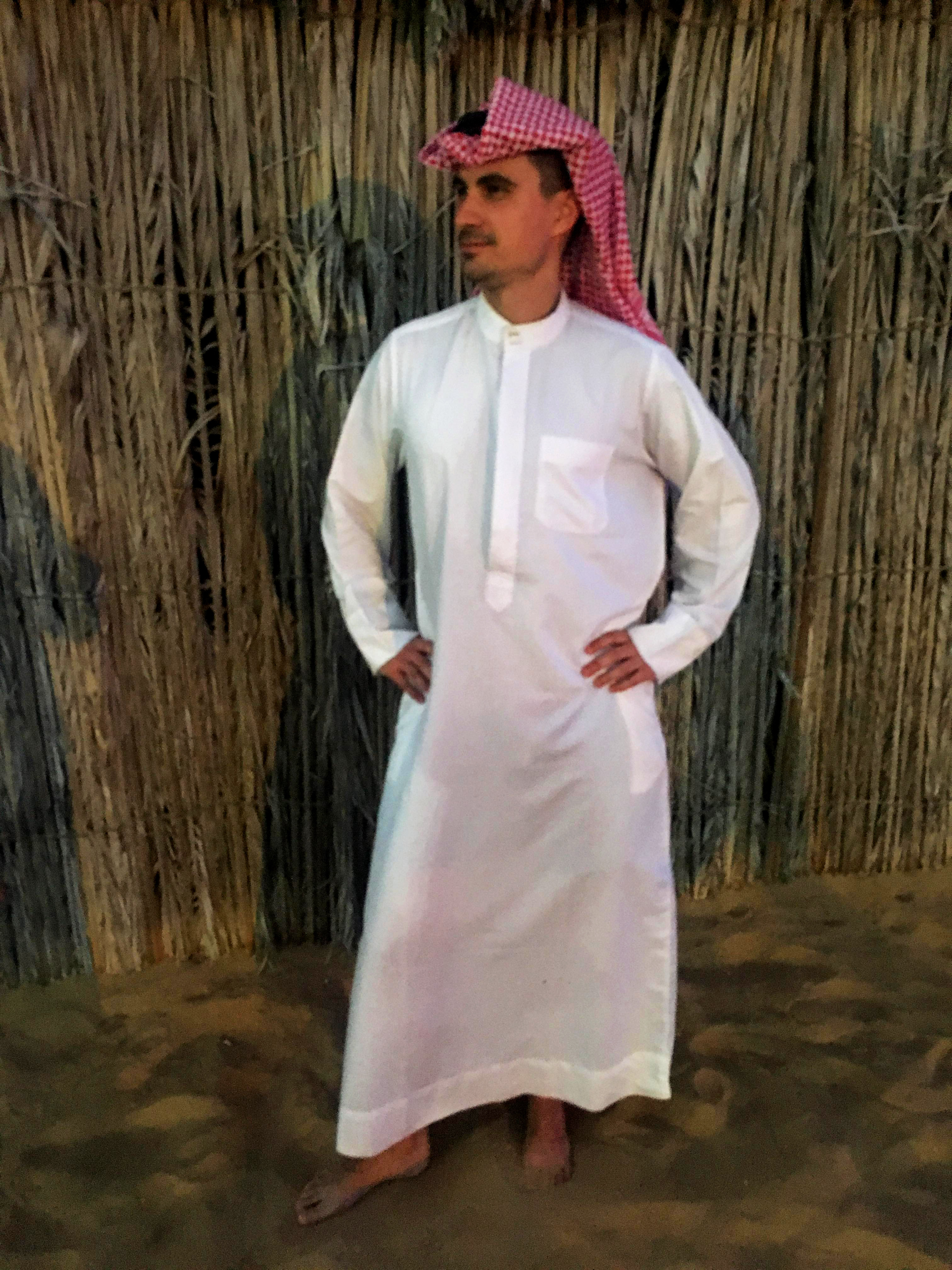 a boy dressed as a shekh with a white dress and red scarf during a desert safari experience in dubai