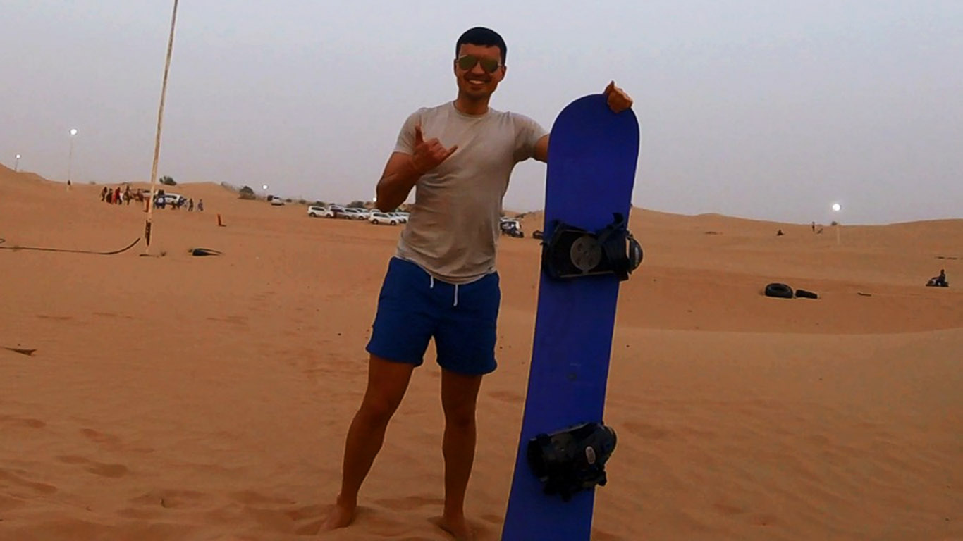 a boy with blue shorts and a while colored t-shirt posing with a blue sandboard in the dubai desert during a safari experience