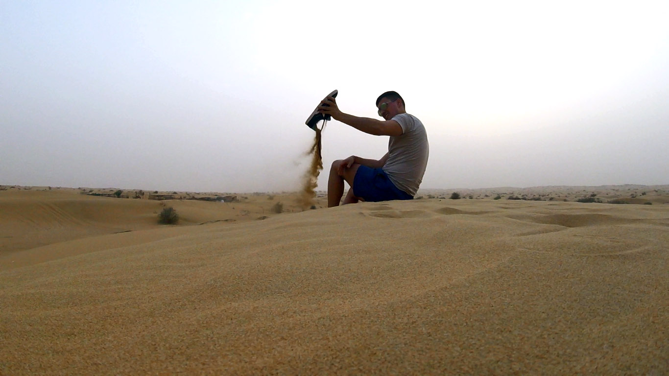 a boy sitting on a sand dune in dubai desert taking out the sand off his shoes