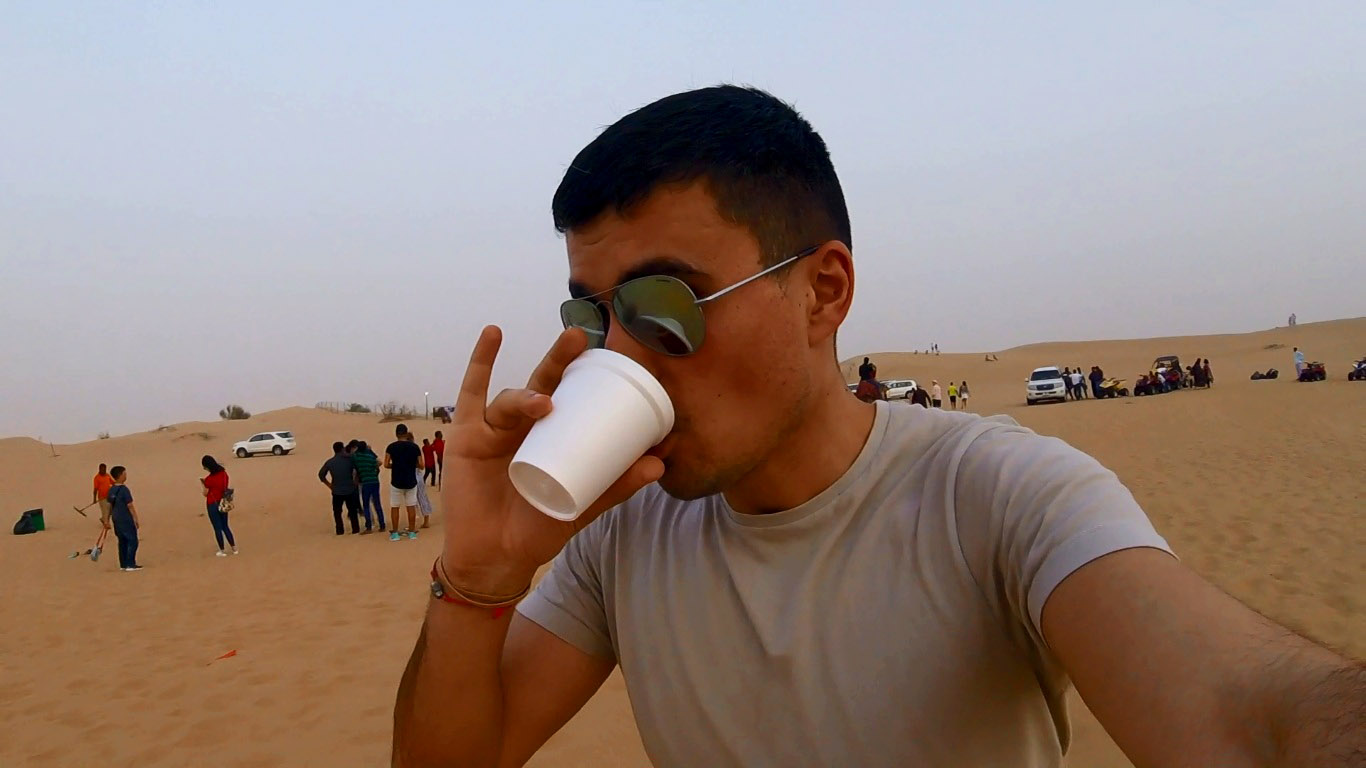 a boy with sunglasses in a desert drinking a team from a white plastic cup and having his pinky up
