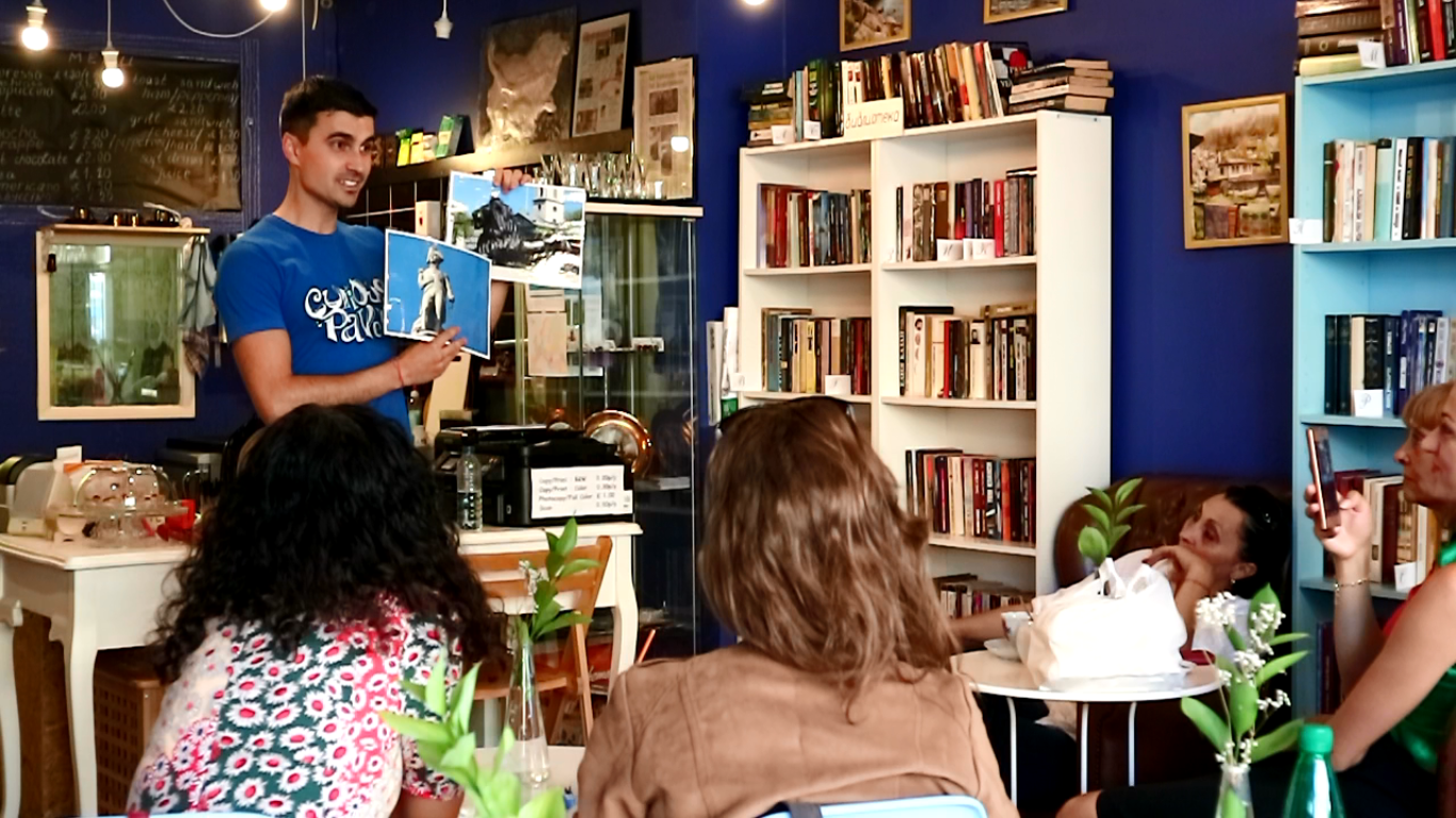 a boy giving a presentation in a bookstore in front of an audience