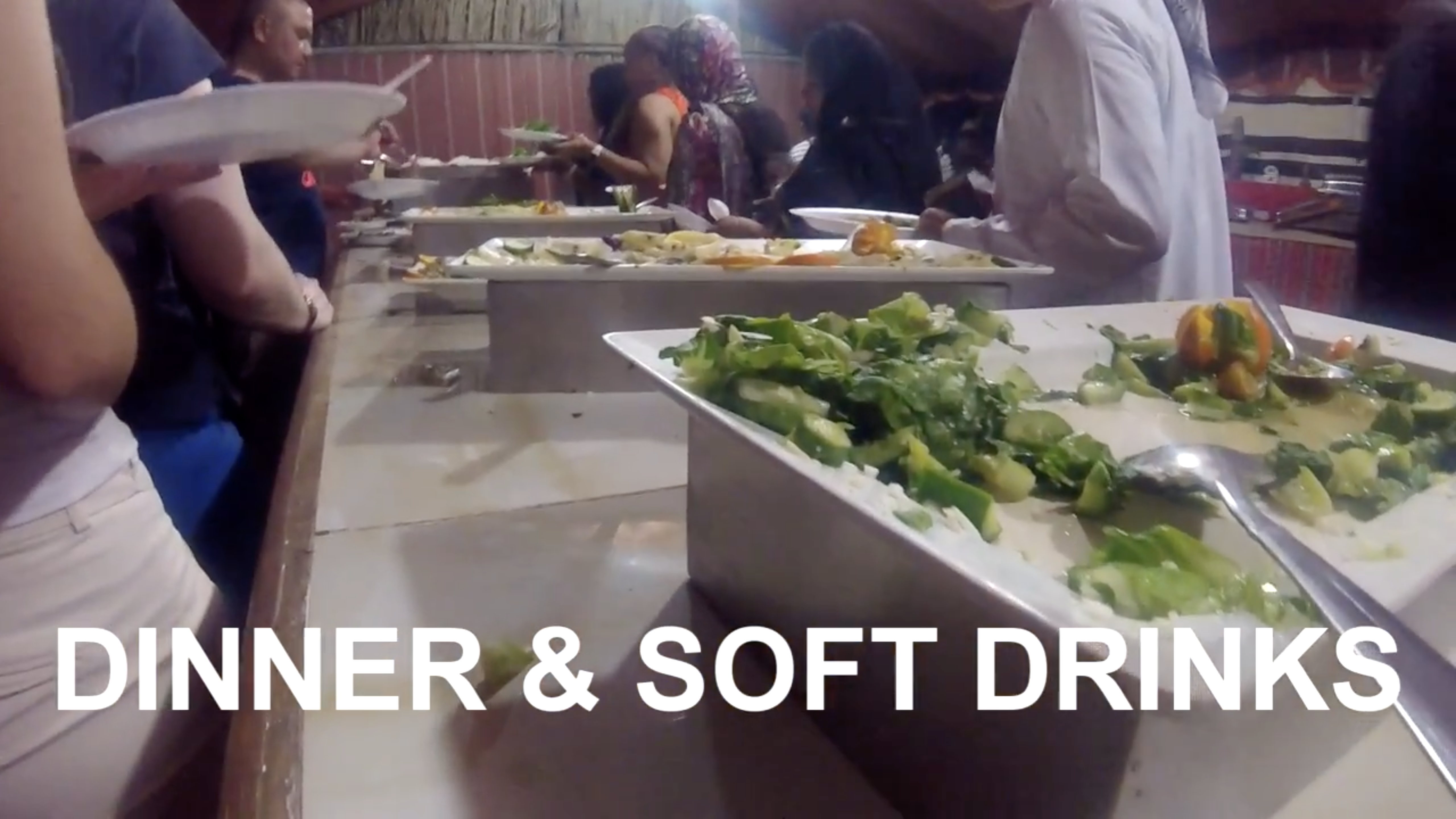 people queueing on both sides of a buffet with salads and other food during the desert safari dubai experience