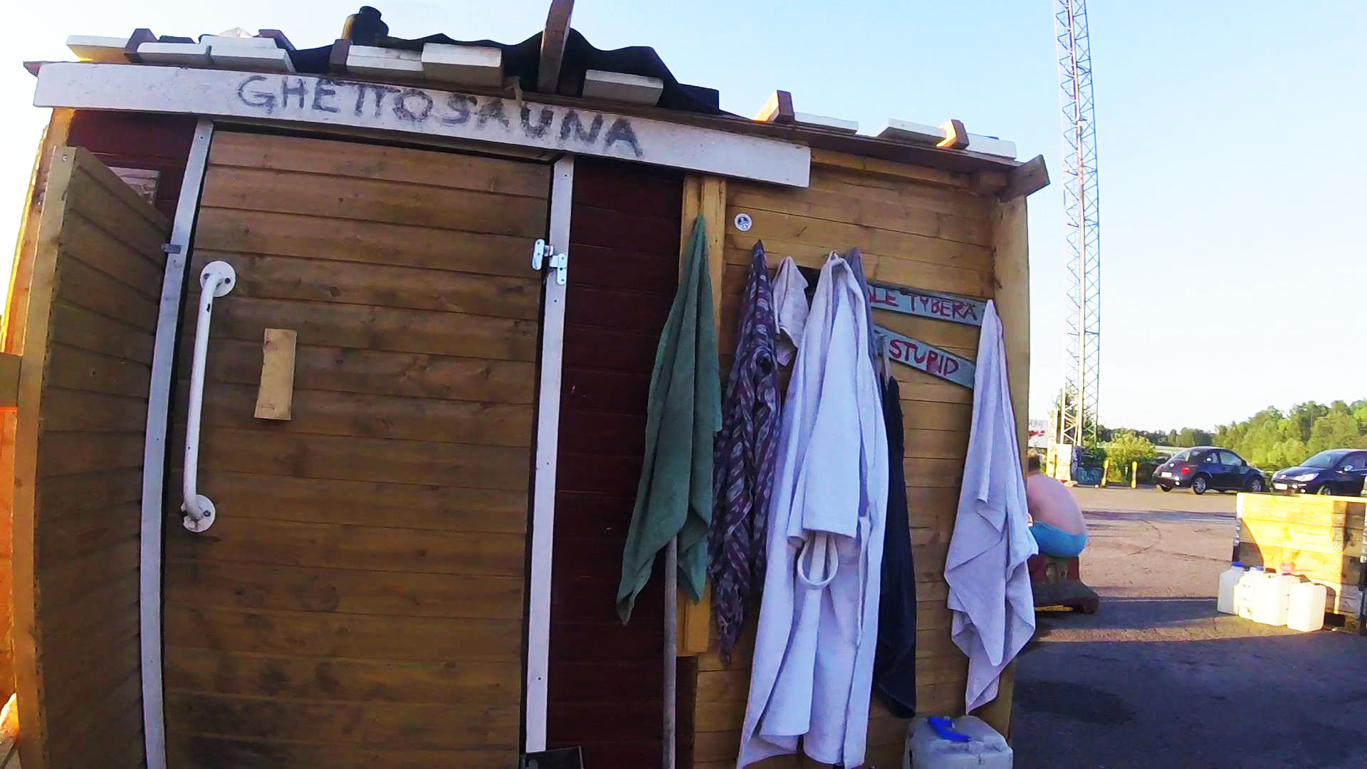 wooden shed with hanged towels and a sign saying ghetto sauna referring to sompasauna the illegal sauna in helsinki
