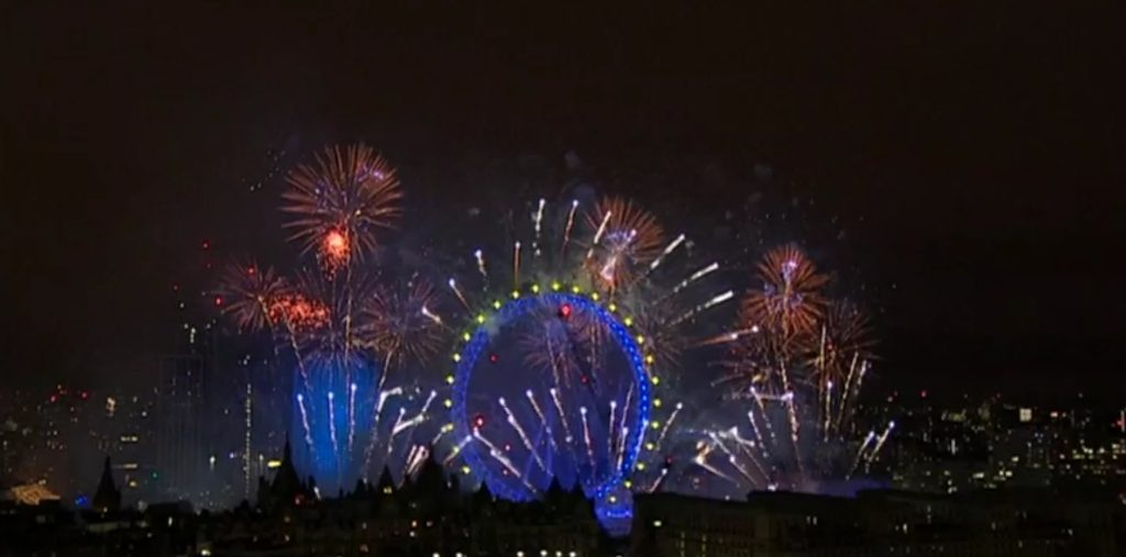 a close up of london eye illuminated in blue surrounded by fireworks during the new years eve firework show in london 2019