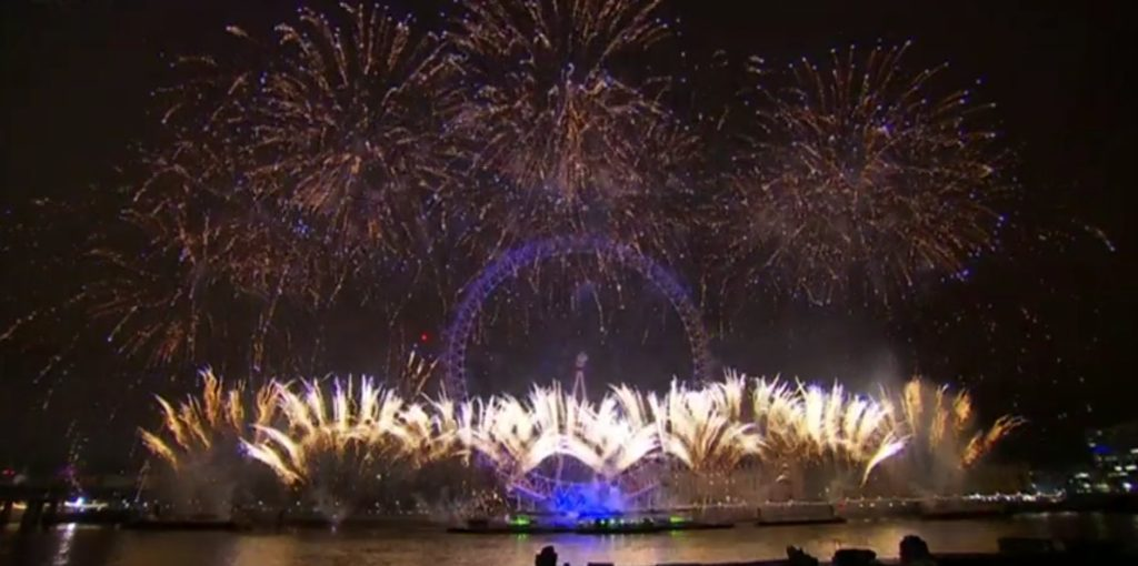 London Eye surrounded by fireworks on new years eve pictured from the opposite shore