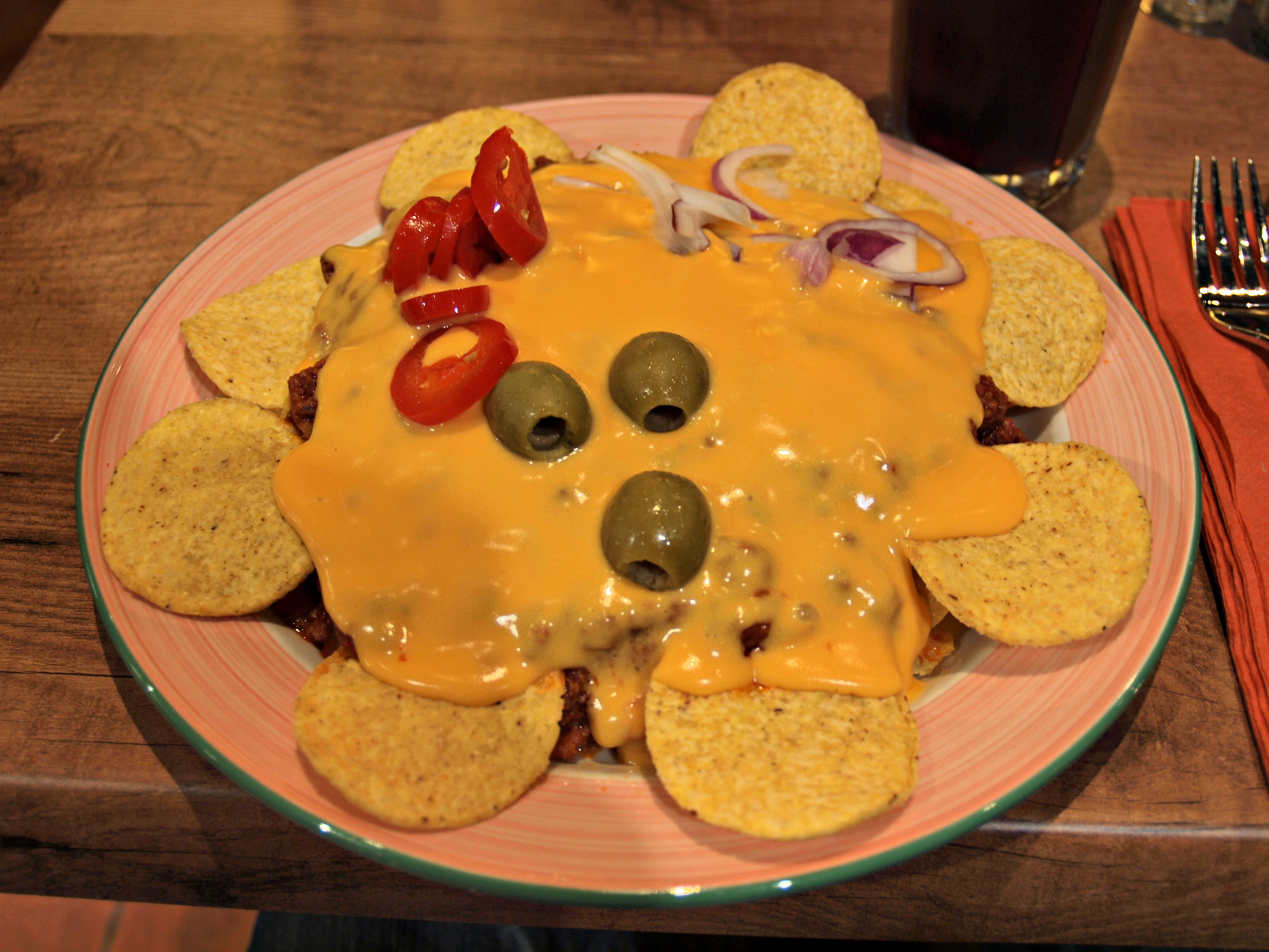 a portion of Nachos in a plate with cheese, olives and jalapenos
