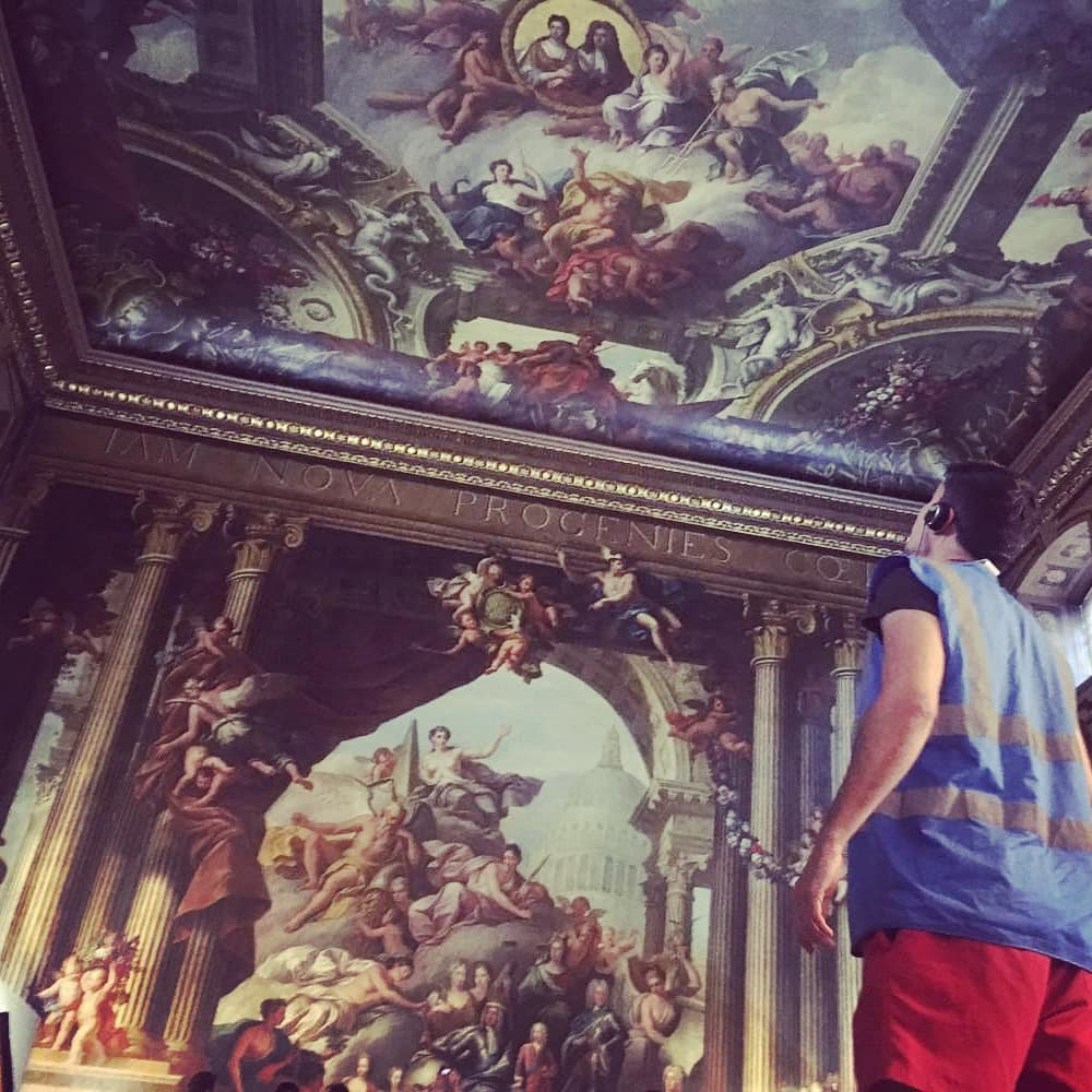 a picture from below of the ceiling of the painted hall in greenwich of a boy looking up towards it