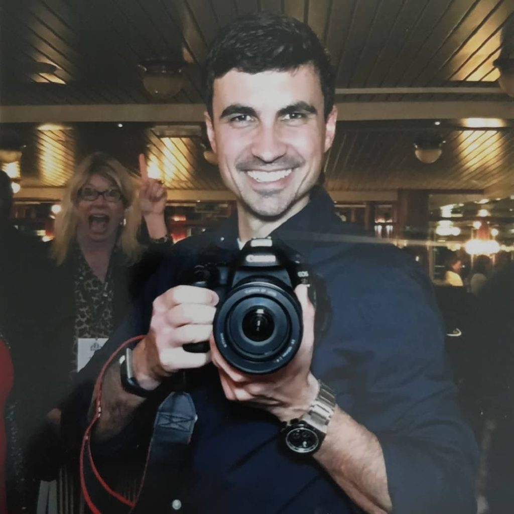 a smiling guy in a navy blue shirt holding a camera being photobombed by a blond woman behind him