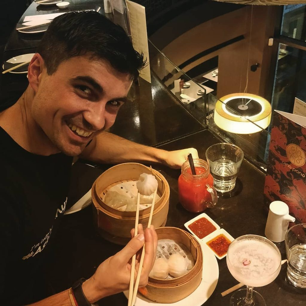 a guy with the nickname of curious pavel posing with chopsticks and holding a dim sum piece on a full table with dim sums and sauces