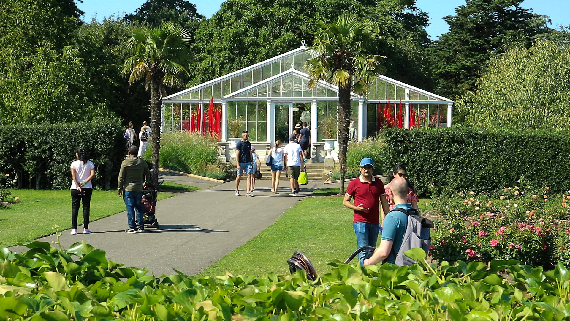 A glass house with lilies inside and people outside in Kew gardens