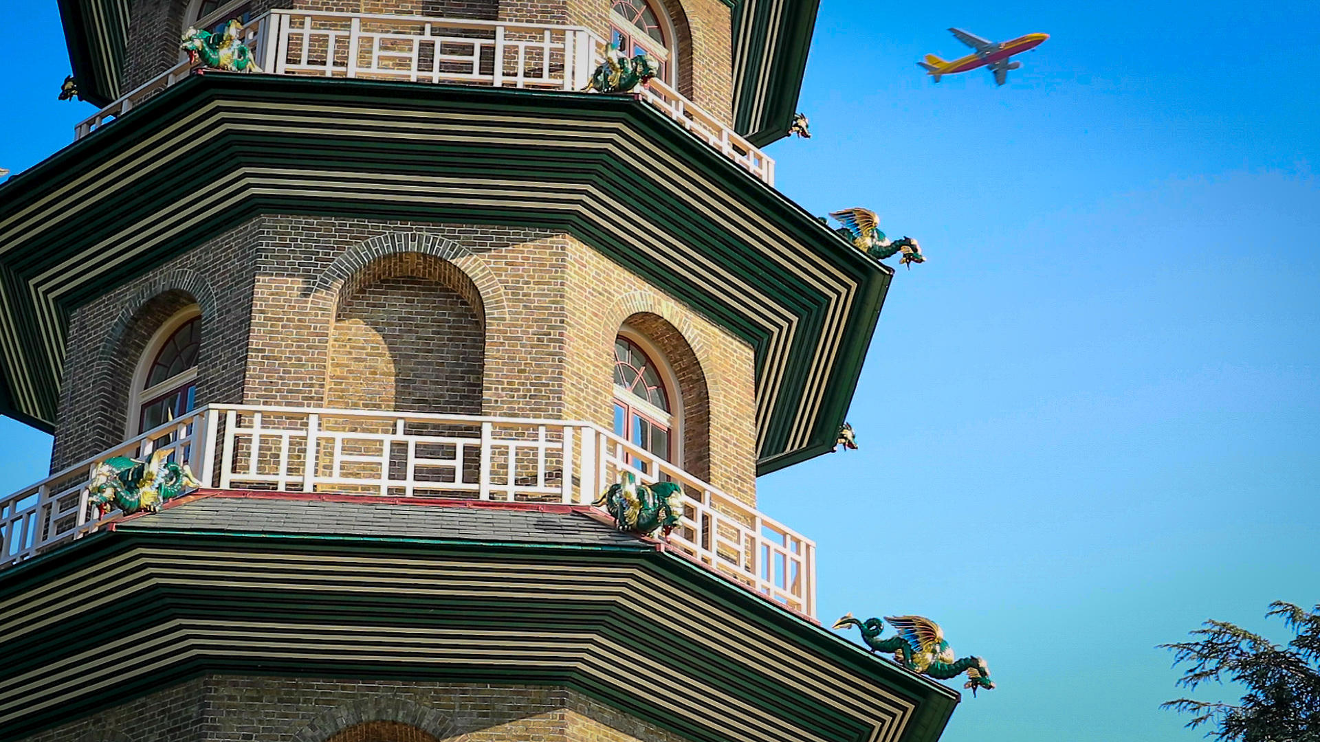 A close up photo of the Chinese Pagoda in Kew gardens with an airplane passing by in the background while clear blue sky