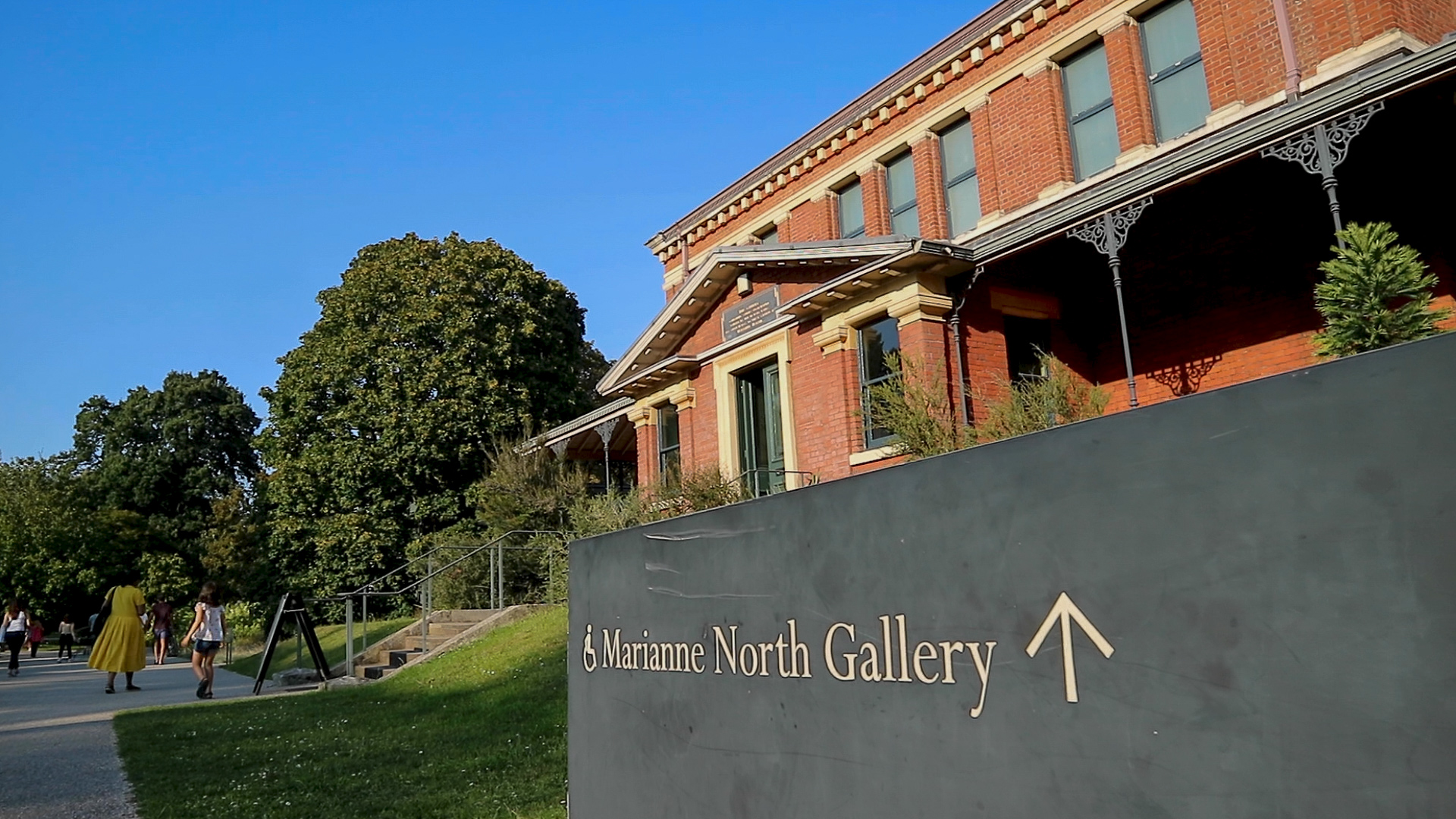 The sign of Marianne North gallery in Kew gardens with the from side of the gallery building