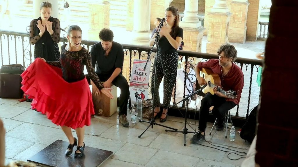 a woman dancing flamenco in a red dress in the streets of seville with a singer two musicians and a guitar
