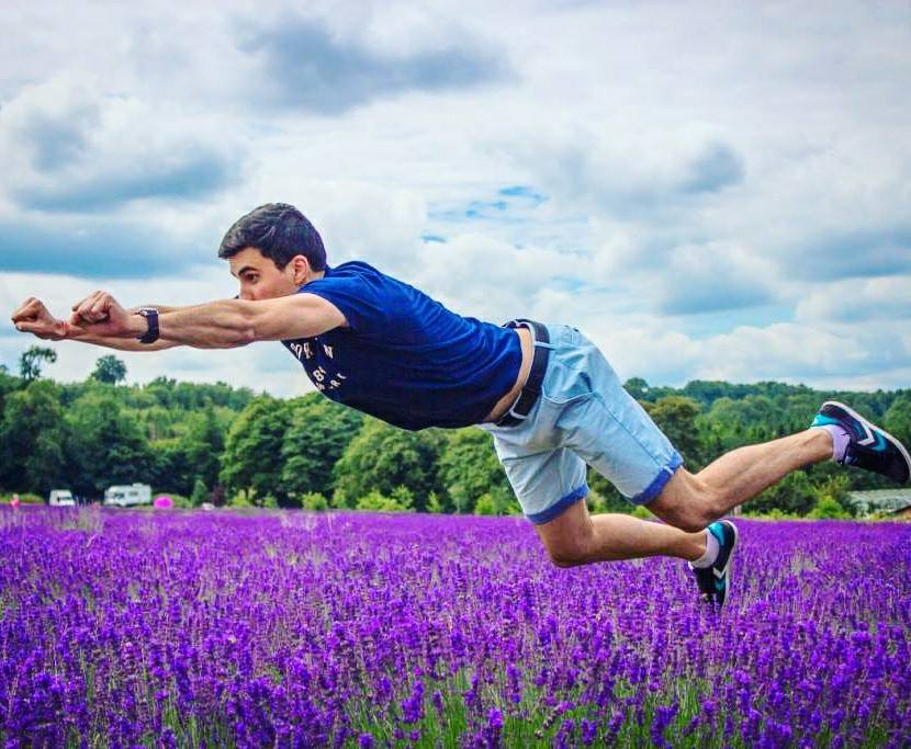 a boy flying over a lavender field in london with green trees in the background