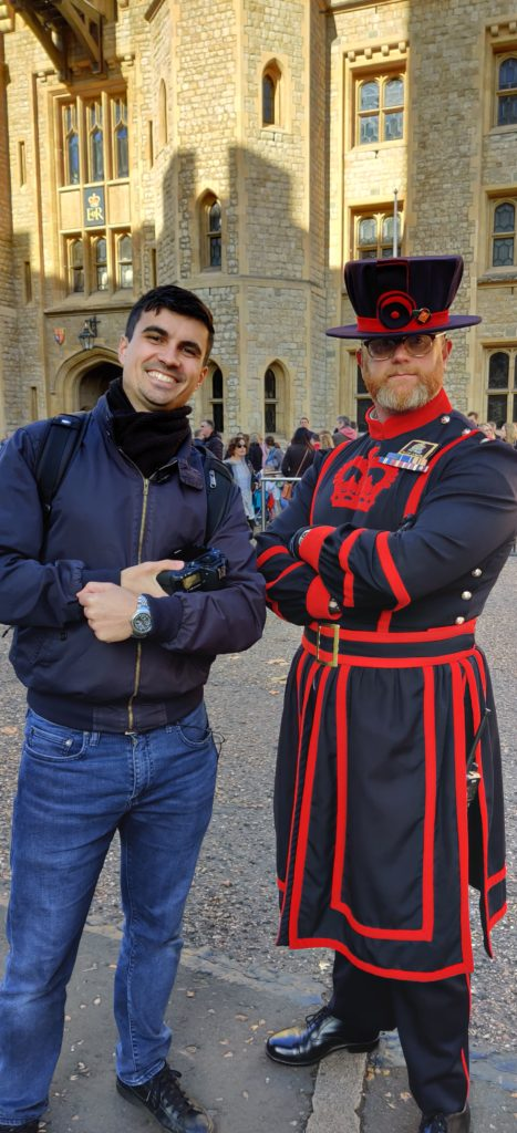 A guy with a camera next to a yeoman guard from the Tower of London  dresses in a Tudor style red clothing