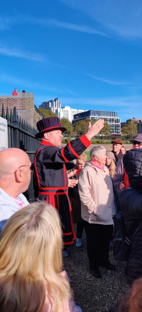 A yeoman in a red Tudor clothing giving a walking tour in front of a crowd in the Tower of London