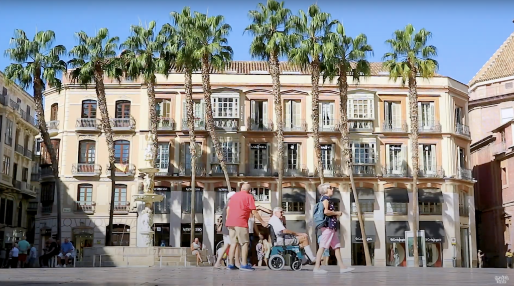 plaza with palm trees and people walking arou